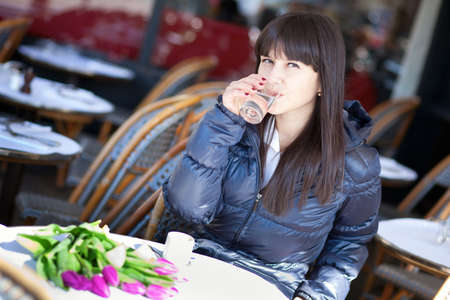 Beautiful brunette lady drinking water and coffee in Parisian street cafe photo