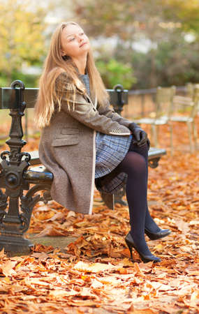 Pretty young lady sitting on the bench and enjoying autumn day photo