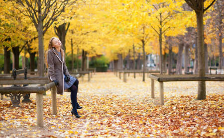 Pretty young girl with long blond hair enjoying a beautiful autumn day in Paris photo