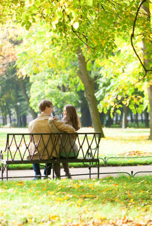 Couple sitting on a bench in park on a spring or fall day photo