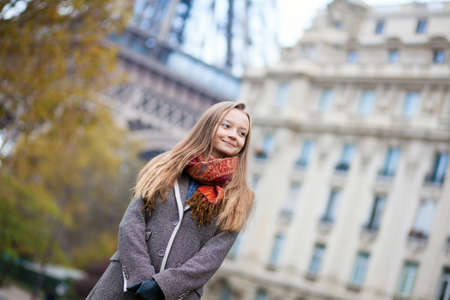 Outdoor portrait of a beautiful girl in Paris, near the Eiffel tower photo