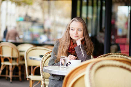 paris street: Thoughtful young girl in an outdoor cafe in Paris