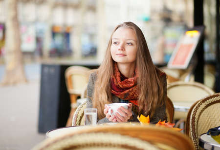 Pensive girl in a Parisian outdoor cafe photo