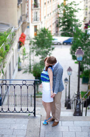 Beautiful couple kissing at the stairs on Montmartre in Paris photo