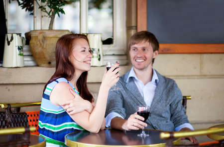 Beautiful couple enjoying their red wine in a cafe photo