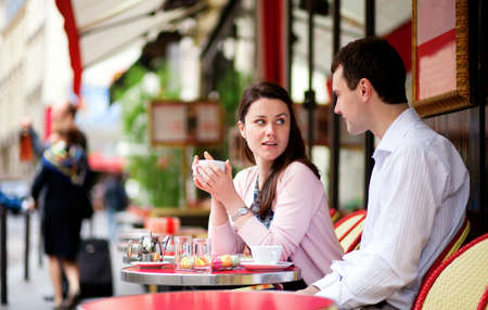 Happy couple drinking coffee or tea in a Parisian outdoor cafe photo