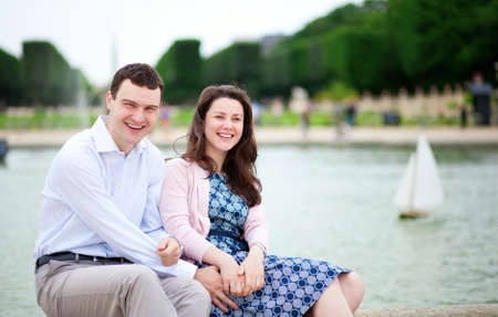 jardin de luxembourg: Laughing couple sitting by the water in Luxembourg garden of Paris Stock Photo