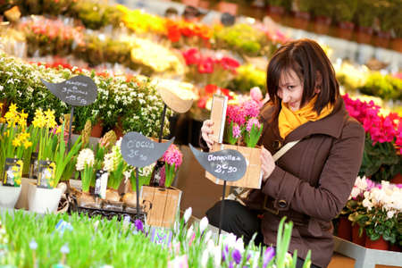 brune: Beautiful young girl buying flowers at flower market