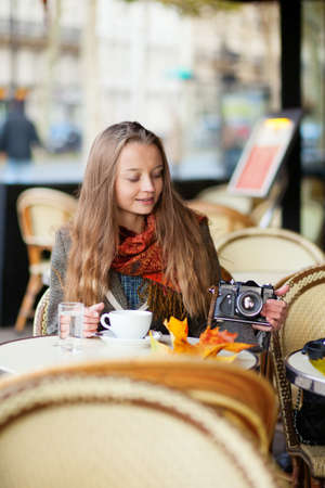 Beautiful young woman in a cafe holding an old-fashioned  camera Stock Photo - 16521539