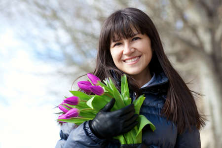 brune: Outdoor portrait of beautiful brunette girl with bunch of fresh colorful tulips