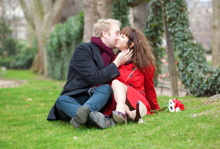 Romantic couple sitting on the grass and kissing photo