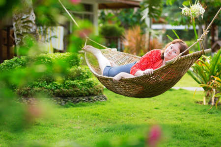 Beautiful woman relaxing in hammock in garden on a tropical resort photo