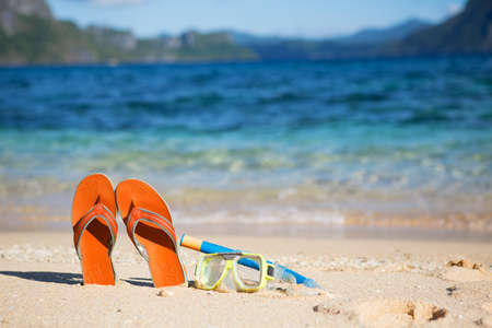 Slippers, mask and snorkel on sand beach near the water Stock Photo - 17044351