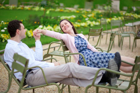 jardin de luxembourg: Romantic couple sitting on chairs in Luxembourg garden of Paris