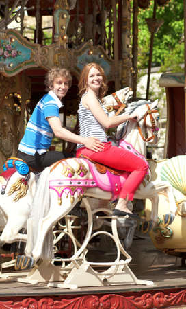 Happy young couple enjyong the ride on merry-go-round photo
