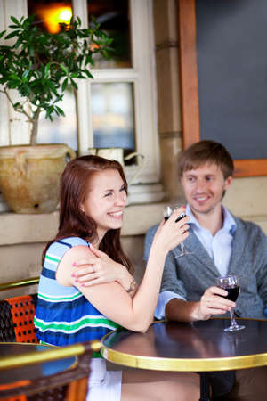 Beautiful couple drinking red wine in a cafe photo