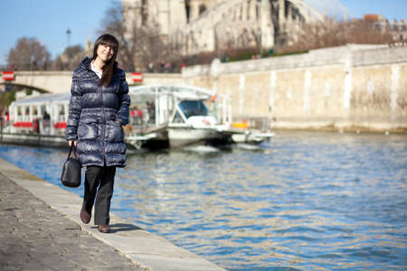 Beautiful brunette tourist walking at the emankment in Paris photo