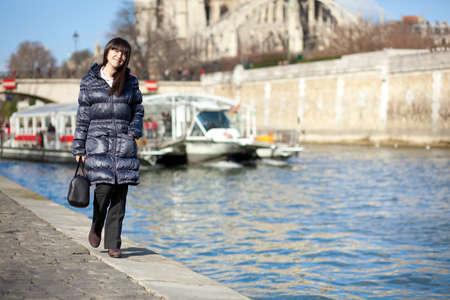 brune: Beautiful brunette tourist walking at the emankment in Paris