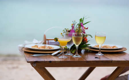Romantic dinner for two with margarita cocktail for served on a beach photo