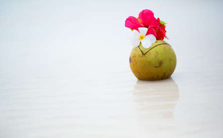 Coconut drink decorated with flowers on perfect white sand tropical beach photo