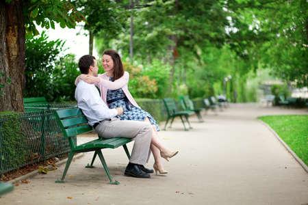 Feliz namoro casal abra�ando em um banco em um parque parisiense Banco de Imagens