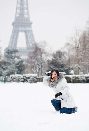 Beautiful girl playing snowballs near the Eiffel tower in Paris photo