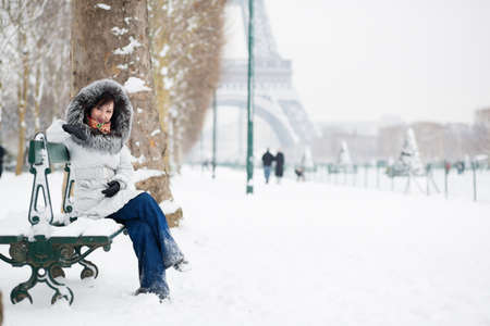 Beautiful girl in fur hood sitting on a bench near the Eiffel tower photo