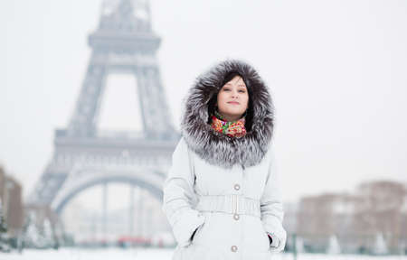 Beautiful girl in fur hood with the Eiffel tower in background photo