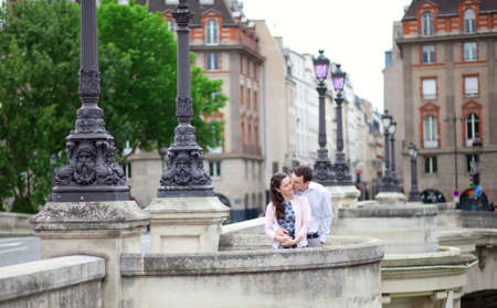 Dating couple is kissing tenderly in Paris on a bridge