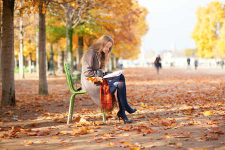fall leaves on white: Girl reading in park on a fall day Stock Photo