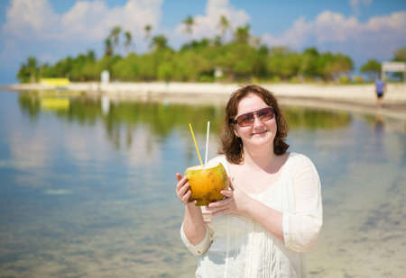 Beautiful woman with coconut on a tropical island photo