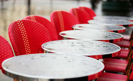 Round tables in a Parisian cafe under the rain photo