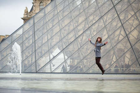 louvre pyramid: Happy young girl jumping near the pyramid of Louvre Stock Photo