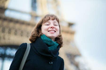 Happy beautiful girl near the Eiffel tower photo