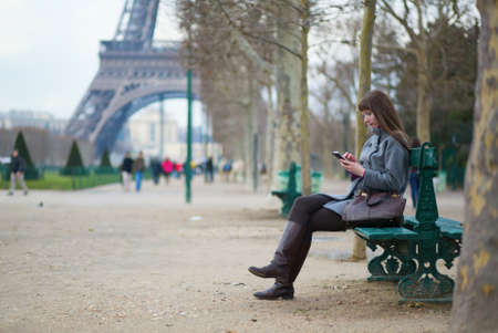 Girl sending sms or surfing in the net in Paris photo