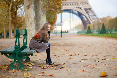 la tour eiffel: Girl sitting on a bench near the Eiffel tower on a fall day Stock Photo