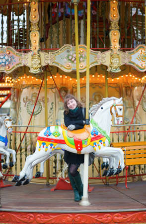 autumn horse: Young pretty girl on a Parisian merry-go-round