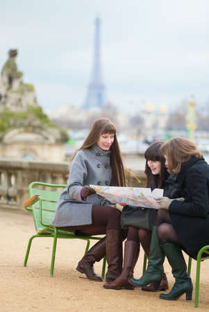 Tourists in Paris, looking in map and planning their trip photo