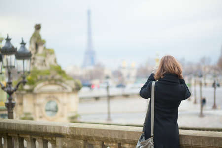 Tourist in Paris taking picture of the Eiffel tower Stock Photo