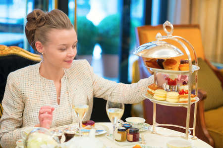 afternoon fancy cake: Beautiful young woman enjoying afternoon tea Stock Photo