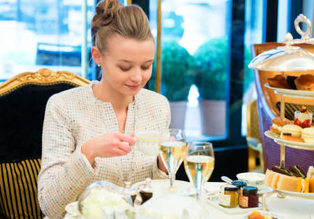 afternoon tea: Young beautiful lady at high tea ceremony