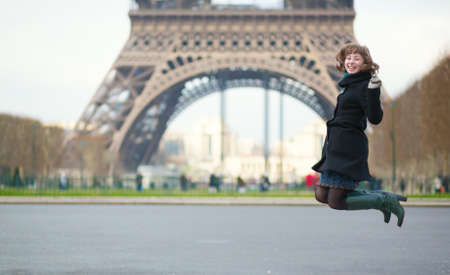 la tour eiffel: Happy young girl jumping in front of the Eiffel tower