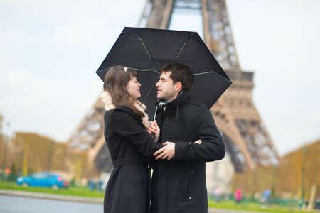 la tour eiffel: Couple with umbrella near the Eiffel tower Stock Photo