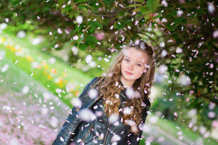 Girl under falling pink petals on a spring day photo