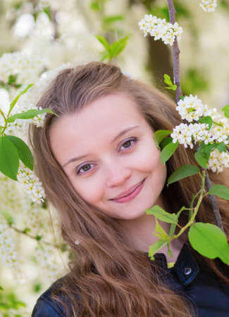 Portrait of a girl with blooming bird-cherry tree photo