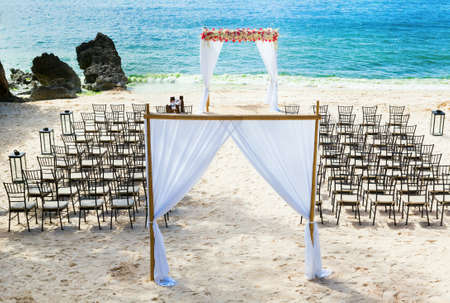 Wedding arch and chairs on the beach photo