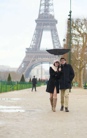 Couple walking under the rain with broken umbrella photo