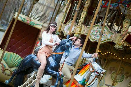 Couple having fun on merry-go-round photo
