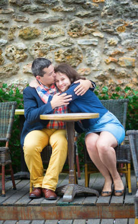 Couple kissing in an outdoor cafe photo