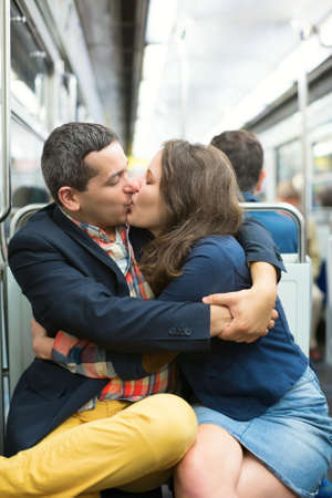 Couple kissing in the Parisian metro photo